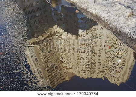 Urban Puddle On A Gray Asphalt With A Reflection Of A House Lit By The Sun, Against Pale Blue Sky, A