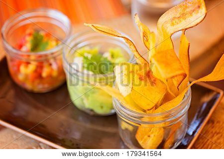 nicely served crunchy and delicious plantain chips with avocado guacamole and mango salsa