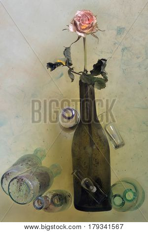 A Dark Green Bottle With One Pink Rose On A Long Stem, Around It There Are Several Glass Old Bubbles