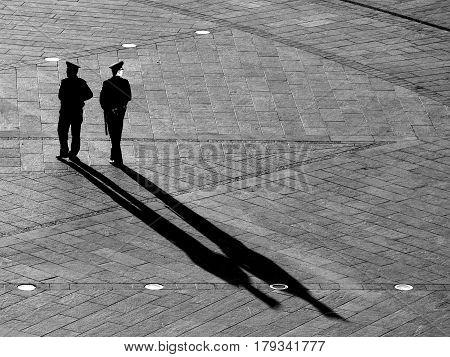 Two Ukrainian policemen black silhouettes of men from whom stretch long diagonal shadows against the background of pavement pavement Independence Square Kiev Ukraine.