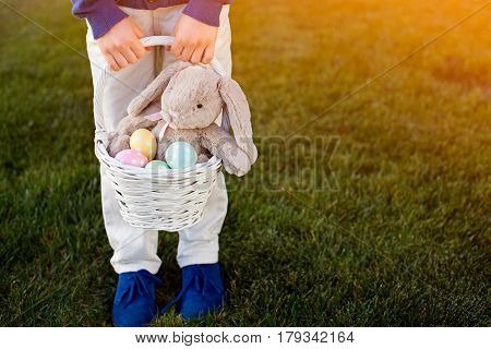 little boy holding white basket with easter eggs and bunny in hands sun flare on right copyspace on right