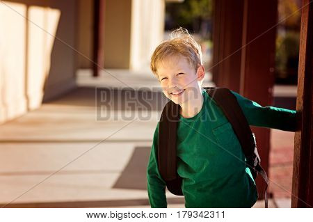 excited smiling schoolboy with backpack enjoying time at school back to school concept