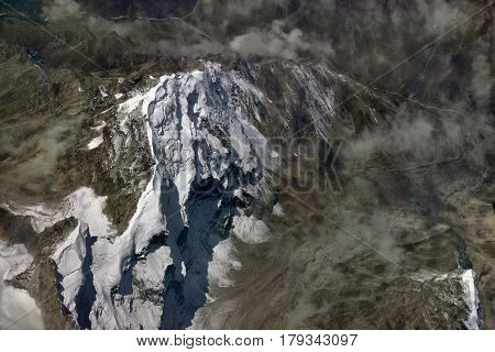 High Mountain Peak Among The Valleys And Chains Of Himalayas, The Glacier Covers The Top, The Haze O