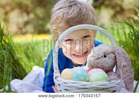 smiling caucasian boy after easter egg hunt with easter basket full of colorful eggs and bunny toy enjoying spring time in the park