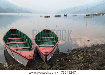 Two Boats Of Bright Colors: White Linen And Green And Red Inside, Parked On The Shore Of The Lake, I