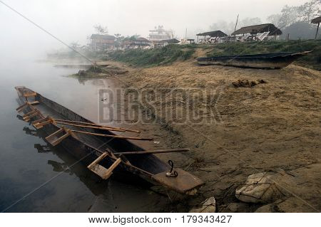 On The Bank Of The River Near The Edge Of The Water There Is A Large Nepalese Wooden Canoe Boat, Ins