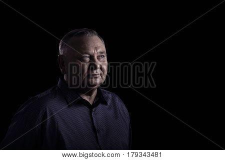 Classic portrait of aged man wearing shirt against black background - retirement concept, copy space