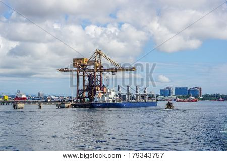Labuan,Malaysia-Mac 25,2017:A large bulk carrier unloaded iron ore in Antara Steel Mill Plant port at Labuan,Malaysia with background of Labuan town on 23rd Mac 2017.