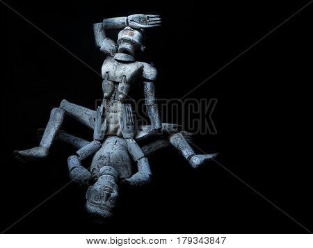Sex Positions Of Kamasutra: Two Old Wooden Mannequins Engaged In Sex On A Black Background.