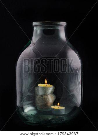 Two Burning Candles Inside A Large Glass Transparent Jar On A Black Background.
