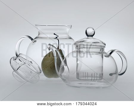 Transparent Glass Teapot And Round Jug Stand Side By Side, The Lid From The Jug Is Removed And Inver