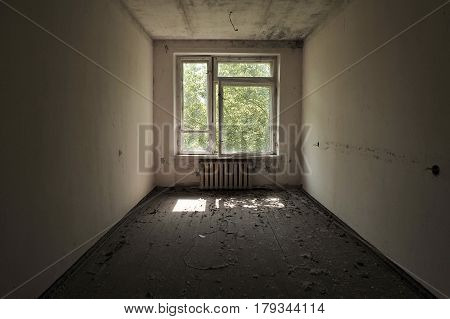 An Empty Room In An Abandoned House In Pripyat: White Walls, Dirty Floor, The Sun Is Shining In The