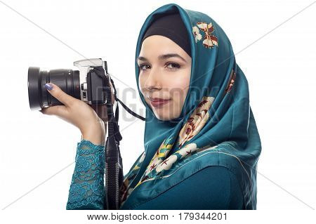 Female photographer wearing a hijab. She is either a hobbyist or a journalist. The headscarf is associated with muslims and east european or middle eastern culture. she is holding a camera.