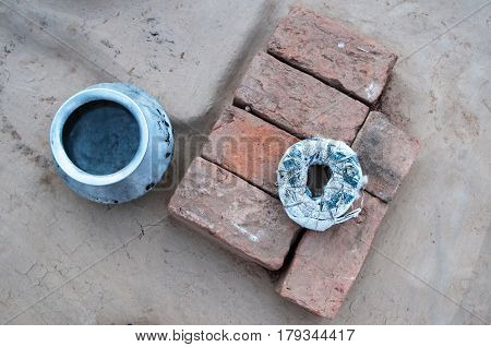A Blue Metal Round Pot, Orange And Brown Rectangular Bricks Laying Together And A White Rag Wrapped