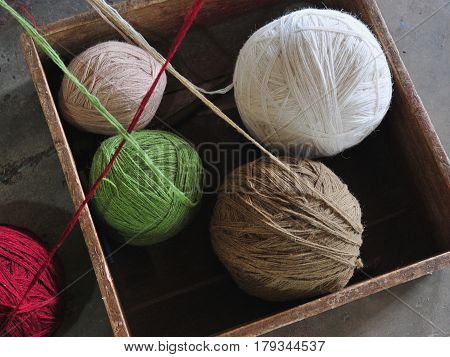 Multicolored Coils Of Thread Lie In A Wooden Box: White Wool, Green, Beige And Red.