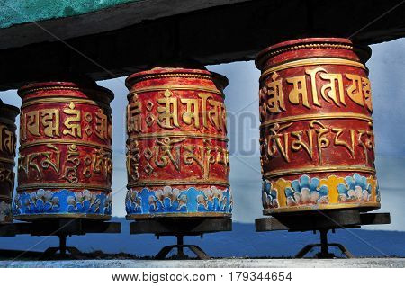 Three Buddhist Prayer Drums Of Red Color With Yellow Hieroglyphs Mantra Against A Blue Sky Backgroun