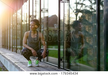 Young African Woman Sitting In The Squat
