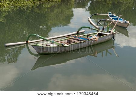 Two Balinese National Wooden Boats In Backwaters, The Water Surface Reflects A Blue Sky With White C