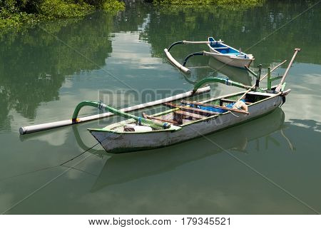 Balinese Wooden Boat With A One-sided Counterweight, White, Tied With A Rope To The Shore, In The Ba
