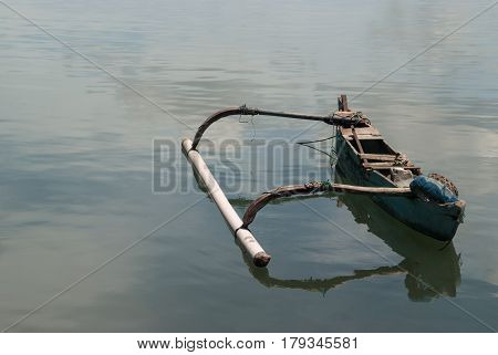A Small Old Wooden Balinese Boat, Blue Paint On The Side, Broken Seats, On The Left A Large Counterw