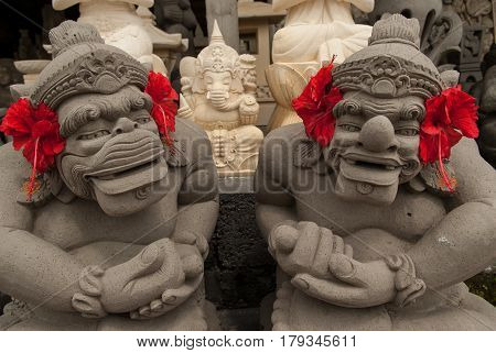 Two Massive Stone Sculpture Of The Deity In The Temple, Heads Decorated With Red Flowers, In The Bac
