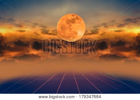 Beauty sky with super moon and silhouette of clouds over racetrack for running. Backstretch or racecourse with foggy. Outdoors in the evening. Dark tone style.
