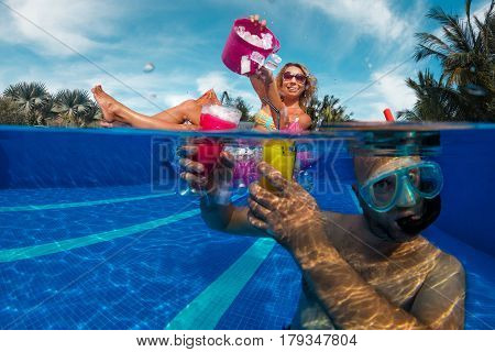 Young couple have fun in swimming pool with cocktails