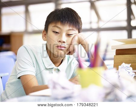 sad and frustrated asian school boy sitting alone in classroom with crumbled paper on desk.