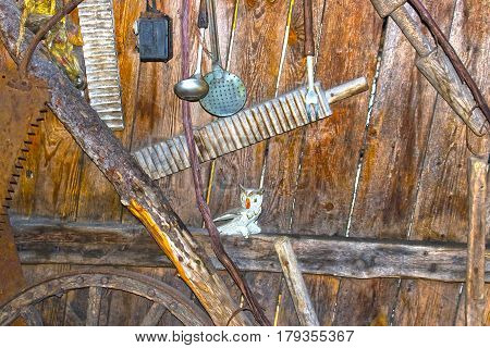 Different kind of vintage old kitchen utensils hung on wooden shelf in kitchen