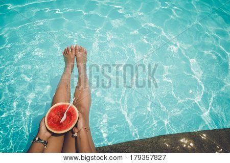 Relaxation and Leisure - Lifestyle in summer of Tanned girl holding watermelon (Tropical fruit) in the blue pool. Summer holiday idyllic.