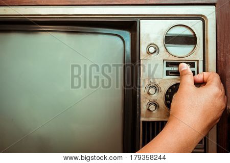 Woman hand fine tuning vintage television with control button. Retro image processed.