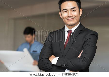 Portrait of handsome confident young businessman standing arms crossed smiling happy looking at camera over construction site background