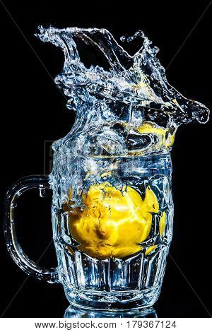 Artistic splash of a lemon created after being dropped into a clear goblet.
