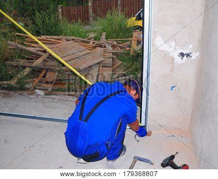 CHERNIVTSI, UKRAINE - APRIL 03, 2017: Garage door installation. Builder with measuring tape. Garage Door Installation & Replacement.