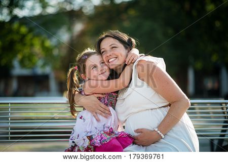 Happy young pregnant mother embracing her affectionate daughter.