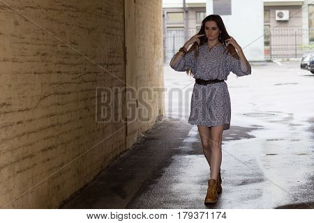 Girl in a short dress and boots walks around the town.