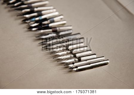 Many metal pens for calligraphy on paper closeup. Selective focus.