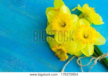 Spring concept with bright yellow daffodils on wooden table with copyspace
