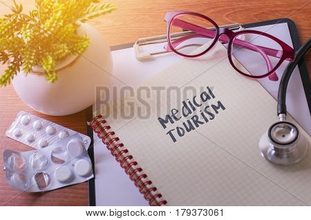 Stethoscope On Note Book With Medical Tourism Words As Medical Concept.