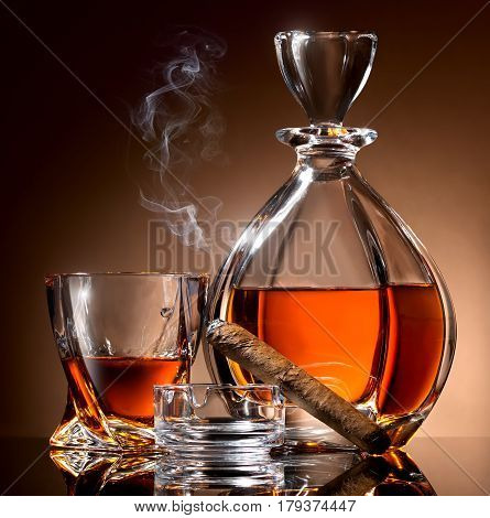 Decanter abd glass of alcohol and cigar on ashtray