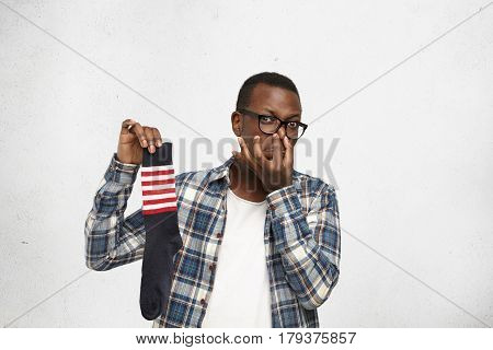 Fastidious Young African American Man Wearing Glasses And Shirt Over White T-shirt Holding Sweaty Di