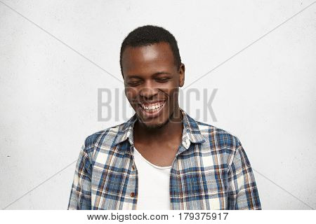 Headshot Of Shy Attractive Young African American Man In Trendy Clothing Closing Eyes And Smiling Br