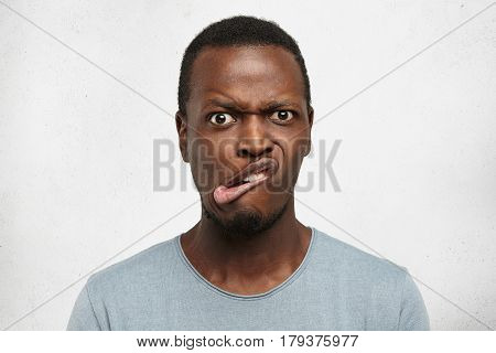 Close Up Studio Shot Of Crazy Goofy Young African Male Making Mouths, Frowning, Staring At Camera Wi