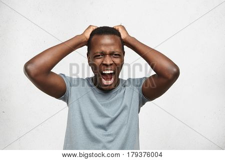 Indoor Portrait Of Stressed Fed-up Afro-american Male Dressed In Grey T-shirt Holding Hands On Head