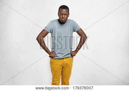 Cropped Portrait Of Mad African American Male Wearing Grey T-shirt And Mustard Jeans Holding Hands O