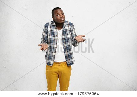 Uncertain Confused Young African American Male Shrugging Shoulders And Gesturing In Uncertainty Whil