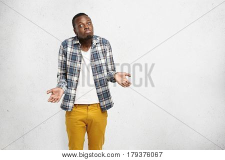 Studio shot of fashionable clueless Afro-American man having confused and dazed look shrugging shoulders and screwing mouth standing isolated at blank wall with copy space for your advertisement