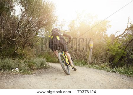 Back View Of Caucasian Biker Wearing Cycling Clothes And Backpack Speeding On His Mtb Bicycle Along