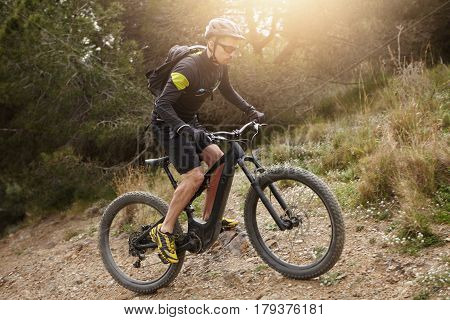 Attractive Young Caucasian Cyclist In Protective Equipment Riding Booster Pedal-assist Bicycle, Clim