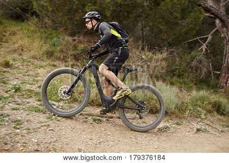 Sideways View Of Risky Young Professional Rider In Cycling Clothing, Helmet And Glasses Climbing Mou